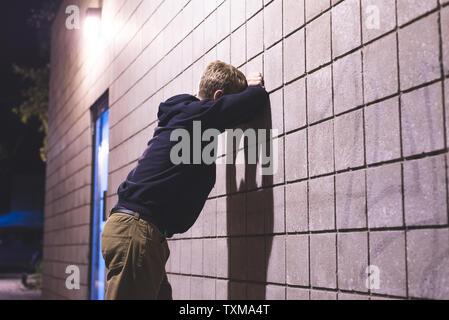 Jugendlicher lehnte sich gegen die Wand in einer Gasse umgekippt. Er leidet unter Depressionen. - Stockfoto