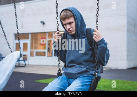 Traurige Teenager auf einer Schaukel sitzend außerhalb einer Schule. Er ist Erinnerungen über, als er jünger war. - Stockfoto