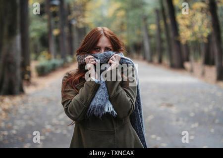 Junge Frau mit langen roten Haaren im Herbst park Mund mit Schal, Porträt Stockfoto