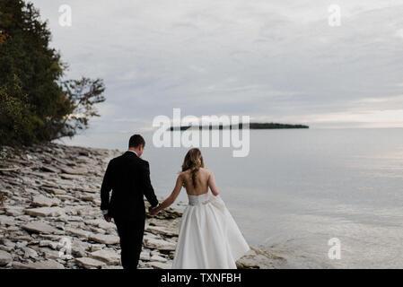 Romantische junge Braut und Bräutigam am Hochzeitstag am See entlang schlendern - Stockfoto
