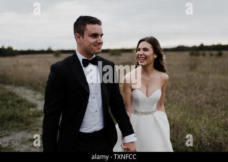 Glückliches junges Paar spazieren Hand in Hand durch das Feld am Hochzeitstag - Stockfoto