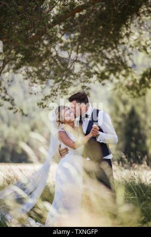 Romantische Bräutigam Braut Küssen auf die Wange in Wäldern - Stockfoto