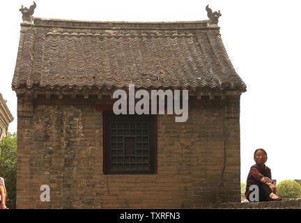 Eine ältere chinesische Frau sitzt neben einem alten Gebäude in der alten Stadt Kaifeng, Provinz Henan, am 29. Mai 2017. Inländische Tourismus boomt in China, mit einem großen Anstieg der ausländischen Touristen in den nächsten zehn Jahren prognostiziert, nach Statistiken. Die Entstehung eines neureichen Mittelschicht und eine Lockerung der Restriktionen durch die chinesischen Behörden sind sowohl für die Betankung der Reiseboom. Foto von Stephen Rasierer/UPI - Stockfoto