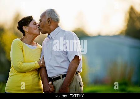 Gerne älteres Paar küssen beim zusammen, die in den Hinterhof. - Stockfoto