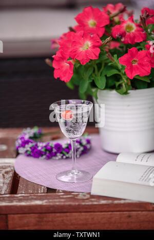Schöne gemütliche Komposition mit Tasse Kaffee, Blumen und alten Buch auf Holztisch. Frühling, Sommer Saison. Zarte Feder romantische Szene. - Stockfoto