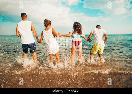 Gruppe aktiver Menschen tanzen und Spaß am Strand im Urlaub - Stockfoto