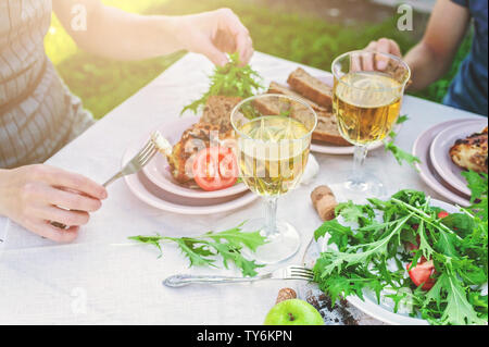 Abendessen im Garten. Die Menschen essen am Tisch mit Wein, gegrillten Fisch, frisches Gemüse und Kräuter. Horizontale Schuß - Stockfoto