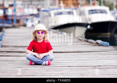 Blond Baby Mädchen 3-4 Jahre alten tragen Sommer Kleidung, Hut und Brille auf See pier Sitzen über Boote im Hintergrund. Mit Blick auf die Kamera. Kindheit. - Stockfoto