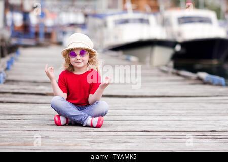 Lustige Baby Mädchen 3-4 Jahre alten am Meer Pier im Freien über Boote im Hintergrund. Sommer Saison. Kindheit. - Stockfoto