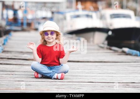Lustige Baby Mädchen 3-4 Jahre alten trägt Hut, Sonnenbrille und Sommer Kleidung im Freien. Kind am Meer Pier sitzen. Mit Blick auf die Kamera. Kindheit. - Stockfoto