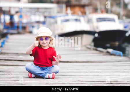 Lächelnd kind Mädchen 3-4 Jahre alten tragen Sommer Kleidung und Daumen hoch, im Freien über Meer im Hintergrund. - Stockfoto