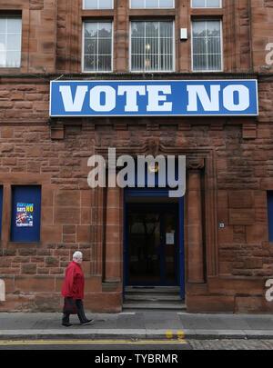 Eine Frau geht hinter einem Gebäude mit einem großen Nein stimmen Plakat gegen die Unabhängigkeit am Tag schottische Bewohnern die zukünftige politische Richtung, die ihr Land in Glasgow, Schottland am 18. September 2014 dauert, entscheiden. 97 Prozent der Bevölkerung registriert hat zu stimmen. Das Urteil soll morgen Vormittag bekannt gegeben. UPI/Hugo Philpott - Stockfoto