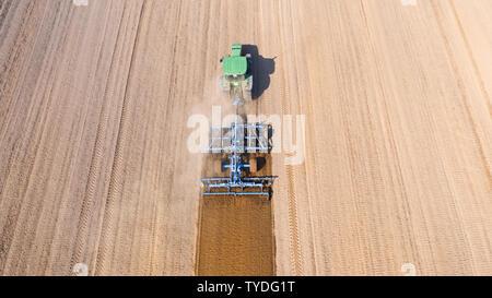 Traktor pflügt das Feld, Ansicht von oben. Der landwirtschaftliche Bereich ist für die Anpflanzung von Gemüse zubereitet. Traktor arbeiten in der Landwirtschaft. - Stockfoto
