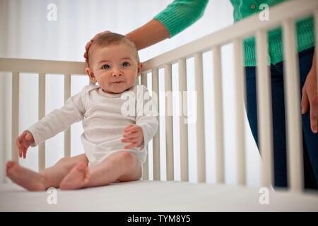 Junge Mutter sanft legte eine Hand auf den Kopf ihres baby boy, als sie ihm hilft, sich gegen die Gitterstäbe seiner Kinderbett sitzen. - Stockfoto