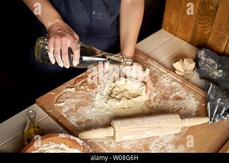 Frau bereitet den Teig auf der Arbeitsfläche mit Mehl und Rolling Pin auf hölzernen Tisch - Stockfoto