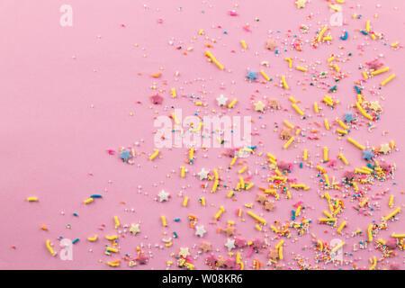 Streusel auf rosa Hintergrund sortierten bunten Kuchen streusel Topping auf Rosa auf der unteren Ecke gesprüht mit Platz für Text - Blick von oben auf die Stern - Stockfoto