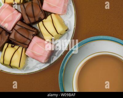 Multi-Colored Iced Fondant Fancy Schwamm Kuchen vor einem schwarzen Hintergrund - Stockfoto