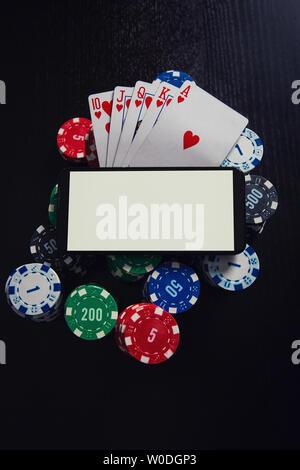 Online kasino, das Konzept. Smartphone leeren Bildschirm auf Chips Stack und Royal Flush Spielkarten Poker Kombination über schwarzen Tisch Hintergrund. Pe - Stockfoto
