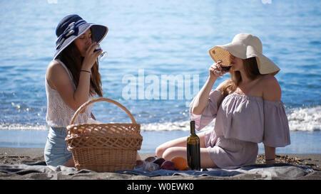 Zwei junge Frauen, die in der Nähe von dem Meer sitzen und Picknicken - Wein trinken - Stockfoto