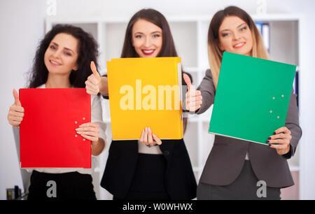 Ein Team von jungen schönen Arbeitnehmer mit bunten Ordner in Ihre Hände in die Kamera im Büro. Mit einem Brainstorming. - Stockfoto
