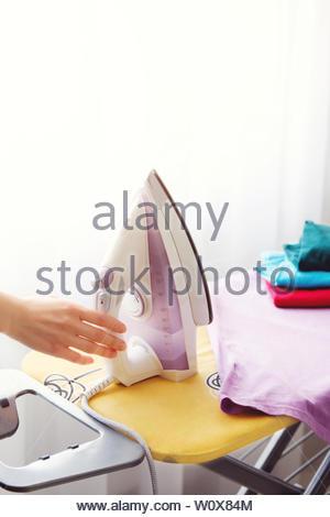 Die Frau, die die Hausfrau Eisen Kleidung zu Hause. Auf dem Bügelbrett Bügeleisen und Lila T-Shirt, sowie andere Dinge in verschiedenen Farben. Weibliche hand - Stockfoto