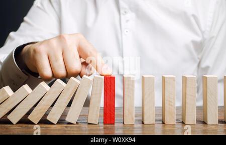 Geschäftsmann stoppt Domino fallen. Risk Management Konzept. Erfolgreiche Unternehmen und Problemlösung. Zuverlässige Führer. Stoppen Sie den zerstörenden Verfahren - Stockfoto