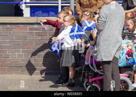 Schule Kinder halten Fahnen während der Königin Besuch Greenfaulds High School in Cumbernauld. Königin Elizabeth II. ist der Besuch Greenfaulds High School in Cumbernauld als Teil einer Woche der Royal Engagements über Schottland.