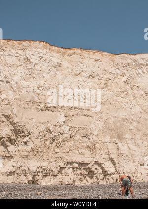 Birling Gap, Eastbourne, East Sussex. Juni 2019. Wetter in Großbritannien: Schauen Sie sorgfältig durch. Spitze der Klippe, Füße über den Rand. Einige scheinen sich der Zerbrechlichkeit und Unterschneidung entlang der Kreidefelsen nicht bewusst zu sein. Felsstürze treten häufig auf. Es ist nicht sicher am Rand. Bitte schützen Sie sich. . - Stockfoto