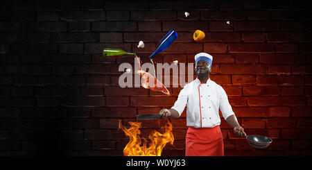 Lächelnd schwarzer Mann in Uniform, cookig Steak auf der Pfanne, mit Zutaten um, Ziegel Wand Hintergrund - Stockfoto