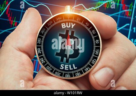 Hand mit Kompass mit glühenden bitcoin Symbol und vor der Börse chart Daten. Kompassnadel zeigt kaufen Wort. - Stockfoto