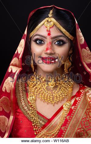 Atemberaubende indische Braut in der hinduistischen Rot traditionelle Hochzeit Kleidung sari mit Gold Schmuck bestickt und ein Schleier lächelt Ausschreibung - Stockfoto