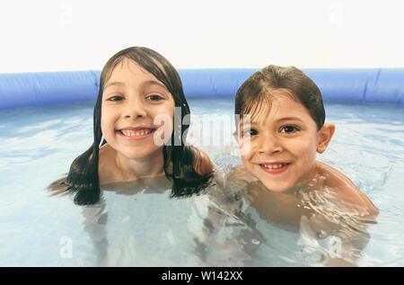 Geschwister spielen in Kunststoff Swimmingpool Kamera suchen - Stockfoto
