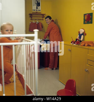 1960s Mutter. Eine junge Frau wird Reinigen und Wechseln von Windeln für ihr Baby, das auf einem wickeltisch liegt. Die Kleidung und Farben sind typisch 60er Jahre. Schweden 1964 - Stockfoto