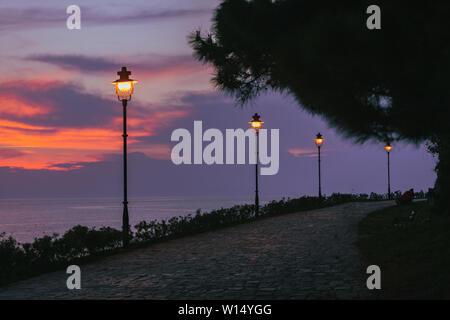 Park mit Blick auf die Lichter der Stadt leuchten Meer auf Hintergrund in Rovinj Stadt in Kroatien. Twilight. Sonnenuntergang - Stockfoto