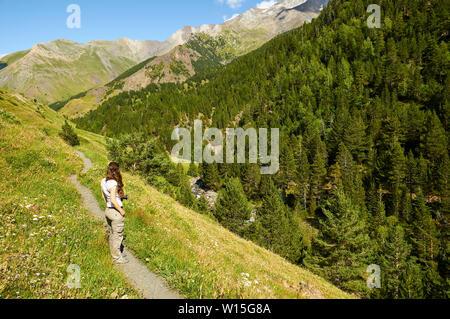 Weibliche Wanderer in GR-11 Wanderweg in der Nähe von Añes Cinqueta de Cruces Fluss mit Posets massiv auf der Rückseite (Viadós, chistau Tal, Huesca, Pyrenäen, Aragon, Spanien) - Stockfoto