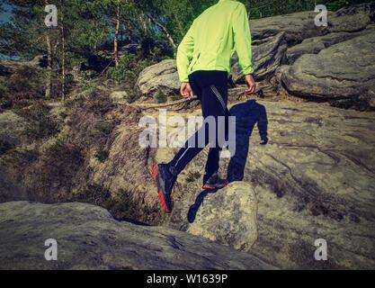 Fitness mensch Trail Runner in den Rocky Mountain Top läuft auf Risse Rocky blockieren.