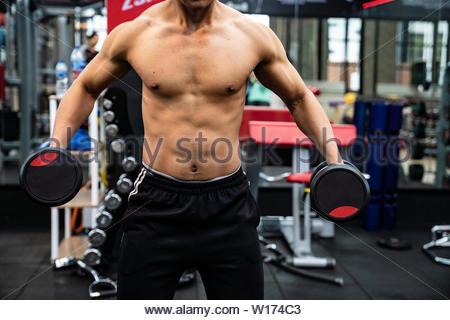 Passen junge Mann in Sportkleidung auf dem Anheben konzentriert - Stockfoto
