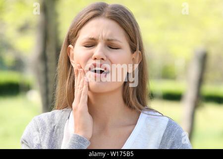 Junge Frau mit Zahnschmerzen im Freien - Stockfoto