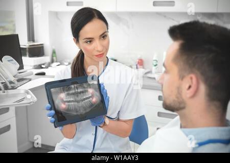 Weiblichen Zahnarzt zeigt Zähne x-ray auf digitalen tablet Bildschirm. Patient sitzt auf Stuhl in professionelle zahnmedizinische Klinik. - Stockfoto