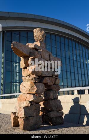 Inukshuk Inuit Red Stone Statue mit Schatten der Mann an Pearson International Airport Terminal 1 Toronto Kanada im morgendlichen Sonnenaufgang - Stockfoto
