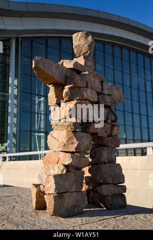 Inukshuk Inuit Red Stone Statue der Mann mit erhobenen Armen an Pearson International Airport Terminal 1 Toronto Kanada im morgendlichen Sonnenaufgang - Stockfoto
