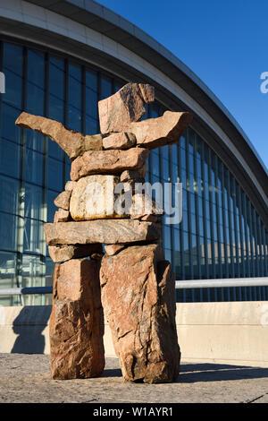 Inukshuk Red Stone Statue mit ausgestreckten einladende Arme bei Pearson International Airport Terminal 1 Toronto Kanada im morgendlichen Sonnenaufgang - Stockfoto
