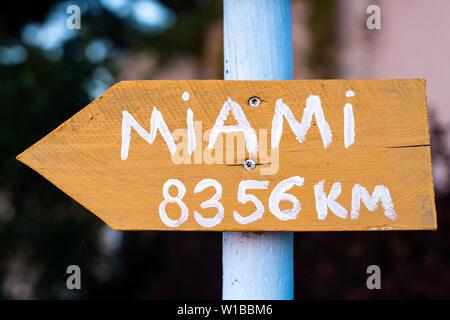 Gelbes Schild mit weißer Schrift auf weißem Pole, die Punkte nach Miami - Stockfoto