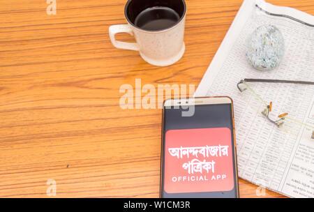 Kolkata, Indien, 3. Februar 2019: Anandabazar Patrika Bengali News App sichtbar auf Mobiltelefon und über einen hölzernen Tisch mit einer Zeitung platziert - Stockfoto
