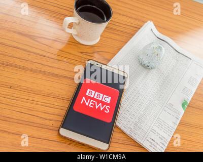 Kolkata, Indien, 3. Februar 2019: BBC News App (Application) sichtbar auf Handy Bildschirm schön über einen Holztisch mit einer Zeitung ein - Stockfoto