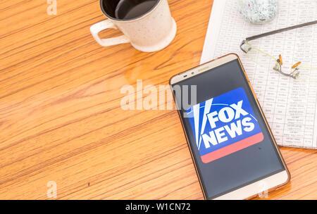 Kolkata, Indien, 3. Februar 2019: Fox News App (Application) sichtbar auf Handy Bildschirm schön über einen Holztisch mit einer Zeitung ein - Stockfoto