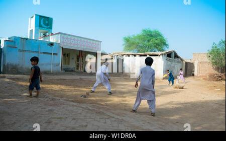 Rahimyar Khan, Punjab, Pakistan - Juli 1,2019: Einige lokalen jungen Kricket spielen in einem Dorf, batsman spielt einen Schuß, Staub fliegen. - Stockfoto
