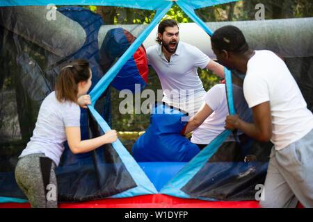Expressive bärtigen Kerl in großen Boxhandschuhe Spaß auf aufblasbaren Ring in einen Vergnügungspark - Stockfoto