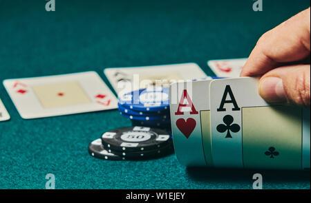 Close-up von zwei Asse in der Hand auf dem Grün spiel Matte auf der rechten Seite des Bildes statt Raum für Bearbeitung, andere Karten und poker chips zu verlassen werden - Stockfoto