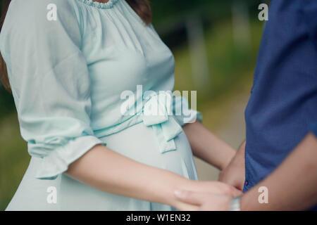 7/8 Schuß von Stattlichen kaukasischen Paar Hände mit Fokus auf schönen runden Bauch der schwangeren Frau, Konzept für die glückliche Familie erwartet Stockfoto